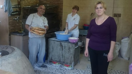 Steaming hot bread and kachapuri being prepared with a smile in the bakery