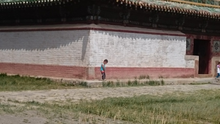A little boy taking a pee outside 1 of the 3 surviving temples