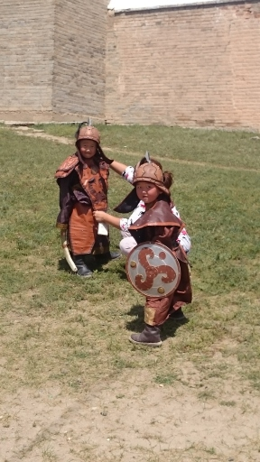Kids dressed as Mongolian warriors outside the monastery